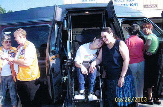 Young Katie Hunn, stricken with Scoliosis, was so surprised when we showed her the van. Here she is with her mother, Janet Gibbons surrounded by some special people.